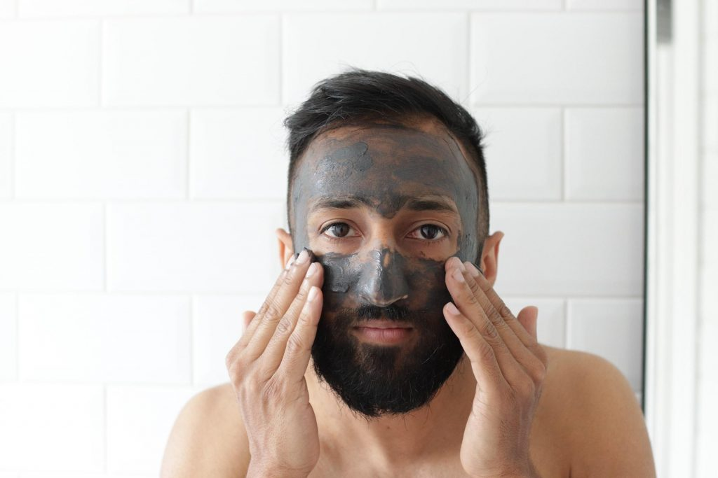 Man cleansing his face (From: Unsplash).