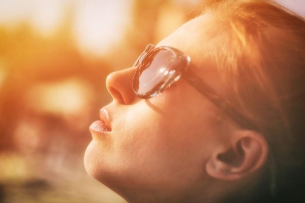 A woman turning her face directly towards the sun. (Photo from: Pexels)