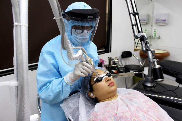 A woman of color getting a facial laser treatment for acne scars. (Photo from: Pexels)