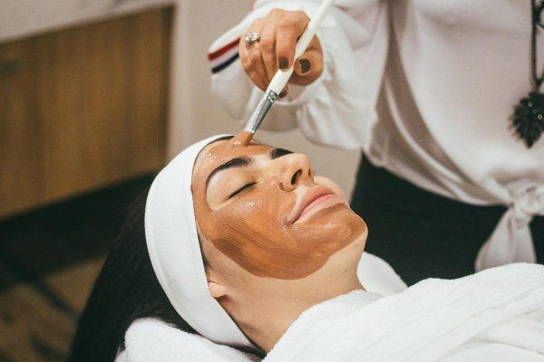 An aesthetician applies a mask during a lady's facial treatment. (From: Unsplash)