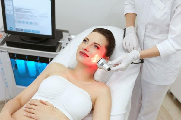 Red infrared light being shone on a woman's face. (From: 123rf.com)