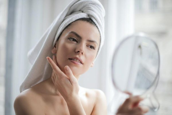 A woman with healthy skin doing her skincare routine. (From: Pexels)