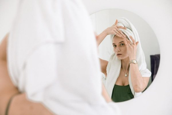 Woman applying skincare product (From: Pexels)