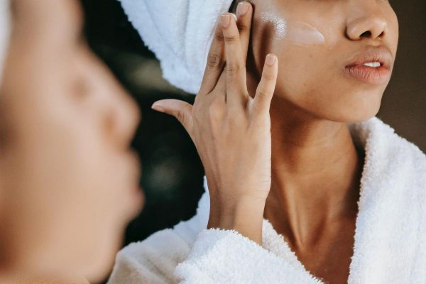 A woman applying moisturizer to her face. (From: Pexels)